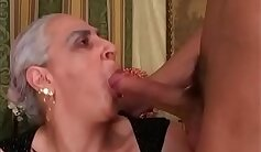 Busty granny grabs young lad and vibrates his cock in her face